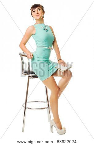 Glamorous girl in turquoise dress and chair isolated