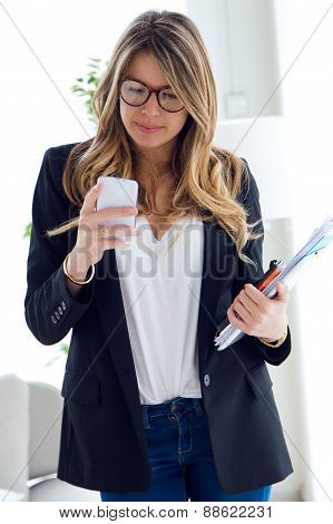 Business Young Woman Using Her Mobile Phone In The Office.