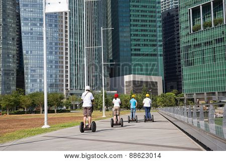 Young people riding on an electric scooter along the waterfront Marina Bay in Singapore.