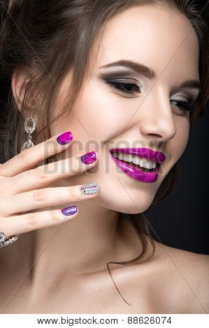 Beautiful girl with a bright evening make-up and purple manicure with rhinestones. Nail design.