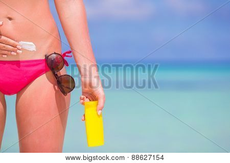 Young woman applying stomach with sunscreen on white beach