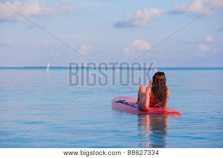 Beautiful surfer woman surfing in turquoise sea during summer vacation