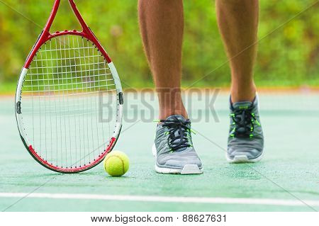 Close up of sneakers near the tennis racquet and ball