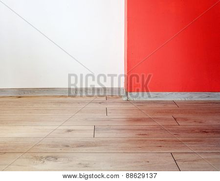 Empty room with red wall and wooden floor
