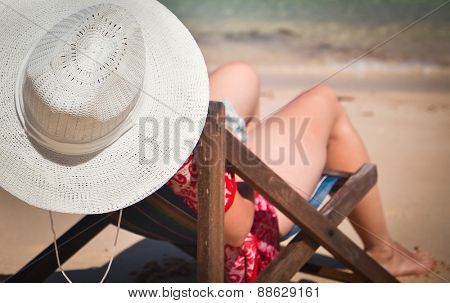 Exotic beach holiday - woman in beach chair and hat