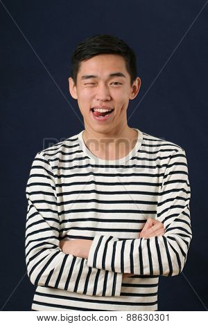 Funny young Asian man showing his tongue and looking at camera
