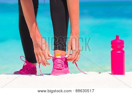 Fitness and healthy lifestyle concept with female model tying laces on sneakers