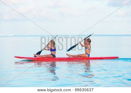 Little girls swimming on surfboard during summer vacation