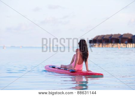 Beautiful surfer woman surfing in turquoise sea