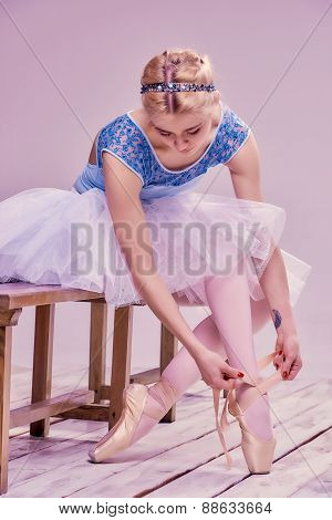 Professional ballerina putting on her ballet shoes.