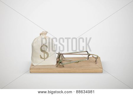 bag with money in wooden mousetrap over light grey background