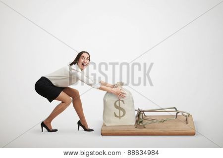excited woman in formal wear reaching her arms to take bag with money in big mousetrap over light grey background