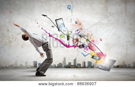 Young businessman evading colorful splashes flying from laptop