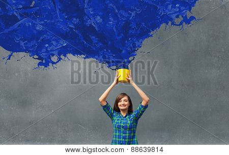Young woman in casual holding yellow bucket with splashes