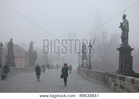 PRAGUE, CZECH REPUBLIC - NOVEMBER 15, 2011: People walk through morning fog over the Charles Bridge in Prague, Czech Republic.