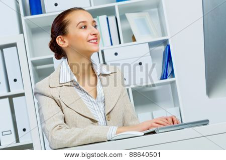 Attractive woman working in office on computer