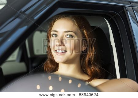 Young pretty woman in car salon sitting in car