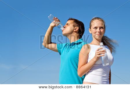 young couple with bottles of water against blue sky