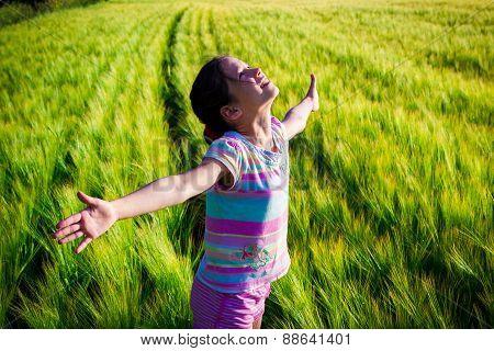 Happy girl on wheat field