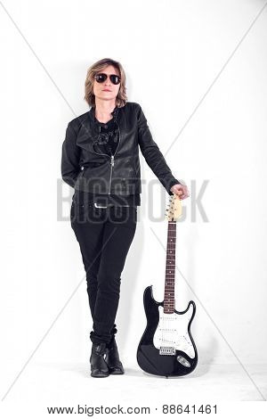 Musician dressed in black leather on white wall