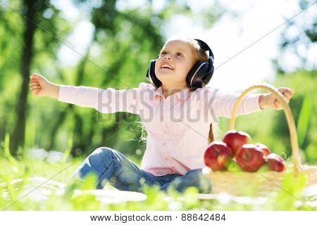 Cute girl wearing headphones sitting in summer park