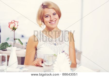 Young pretty red haired woman sitting in cafe