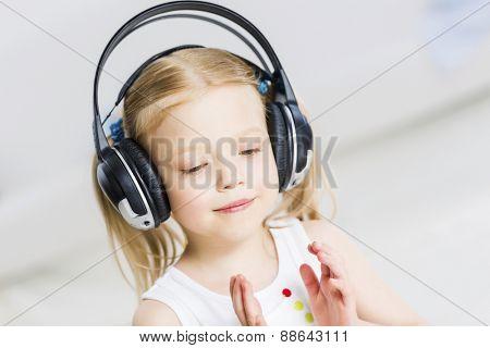 Cute adorable girl wearing headphones and enjoying music