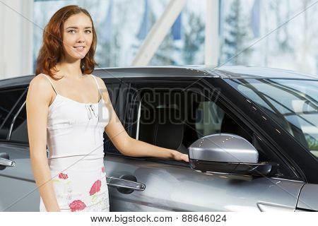 Young pretty woman in car salon standing near car