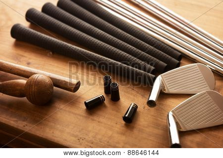 Golf club making. Golf club components on a work desk or work bench. grips, shaft, ferrules  and, iron head.Focus is on black ferrule parts. Shallow depth of field.