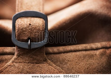 Fastened buckle. Buckle section of a leather bag or case. Extremely shallow depth of focus. Focus is on buckle pin.