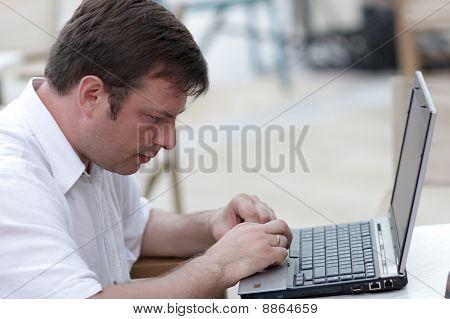 Man Types On Laptop In Cafe