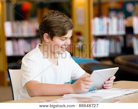 Teenage boy sitting with tablet in library