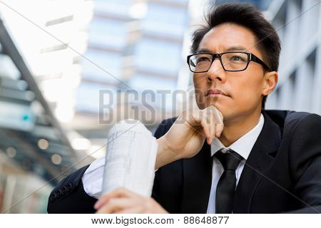 Businessman sitting outdoors with newspaper