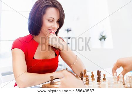 Business woman sitting in front of chess and planning