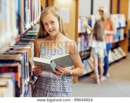 Teenage girl picking a book in public library