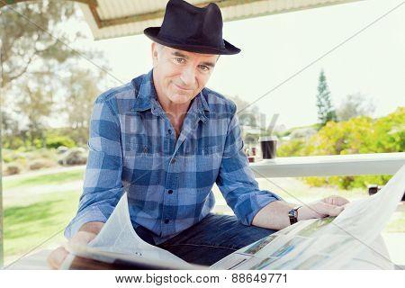 Senior gentleman reading newspaper in park