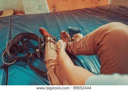 Woman Putting On Climbing Shoes Indoor