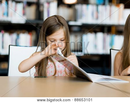 Little girl reading books in library