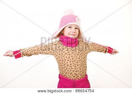 Little girl in a pink hat with arms outstretched in the studio