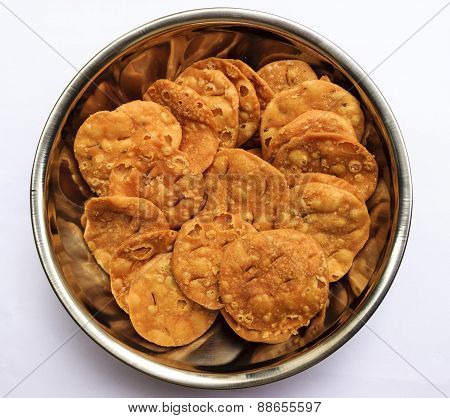 Indian savouries kept in a vessel on a plain background