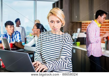 Chinese woman programmer in lounge of IT start-up with laptop, co-workers in the background
