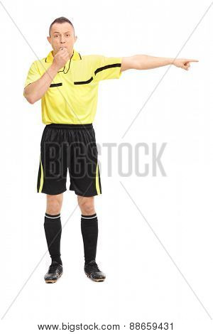 Full length portrait of an angry football referee blowing a whistle and pointing with his hand isolated on white background