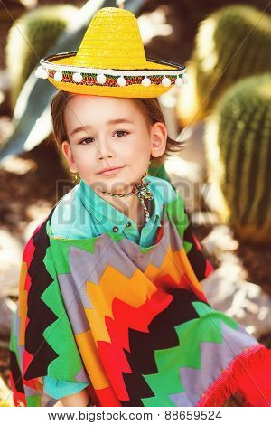 Boy dressed in Mexican costume against the background of a cactus