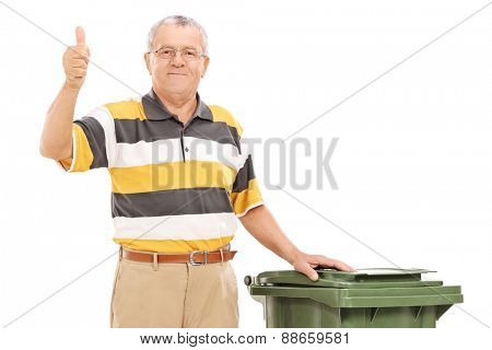 Satisfied senior standing by a trash can isolated on white background