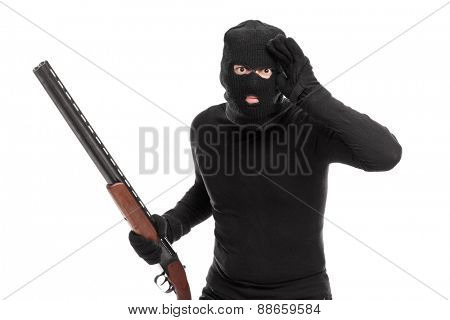 Burglar in black with rifle looking through an imaginary glass isolated on white background