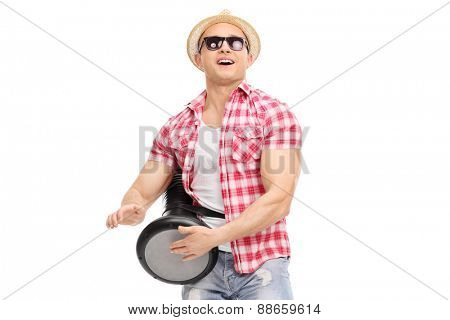 Young joyful man playing on a doumbek and dancing isolated on white background