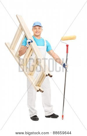 Full length portrait of a young house painter holding a paint roller and a wooden ladder isolated on white background