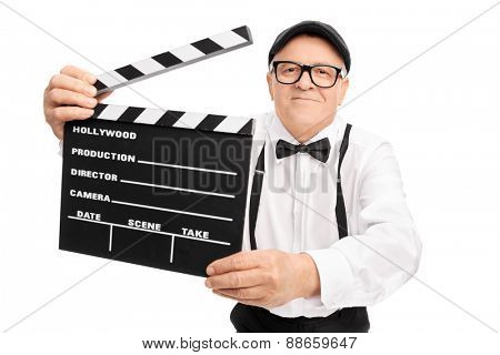 Senior movie director holding a movie clapper, smiling and looking at the camera isolated on white background
