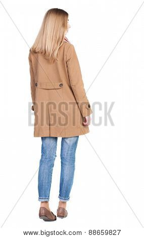 back view of standing young beautiful  blonde woman in brown cloak. girl  watching. Rear view people collection.  backside view of person.  Isolated over white background.