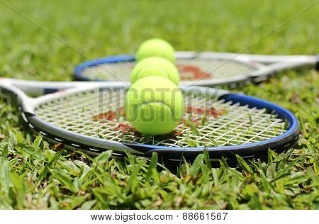Tennis Racket With Balls On The Grass